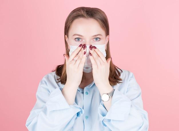 Een brunette vrouw in een blauw shirt zet een masker op