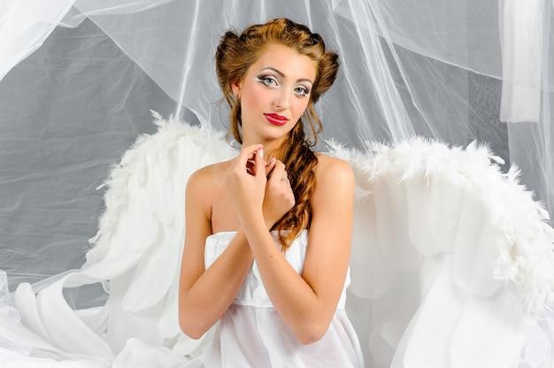 Een brunette vrouw in een engel kostuum vormt voor de camera.