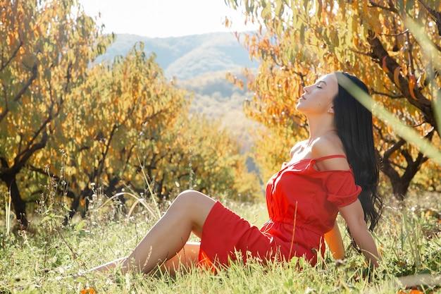 Een brunette vrouw in een rode jurk zit op het gras en poseert tegen het gelige gebladerte van bomen