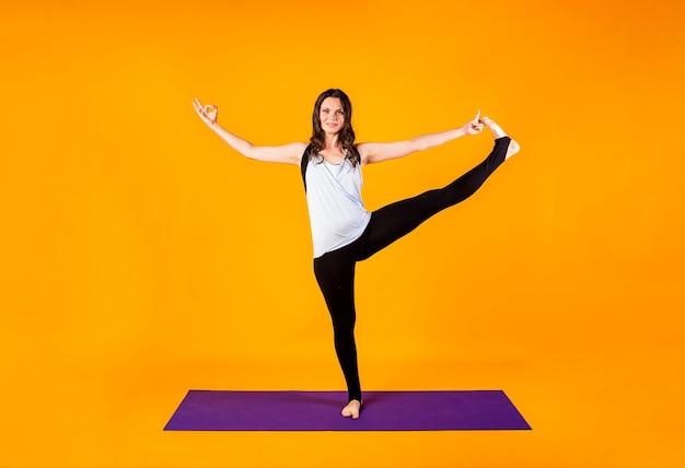 Een brunette vrouw in een sportuniform voert een yoga-pose uit op een paarse mat op een oranje muur