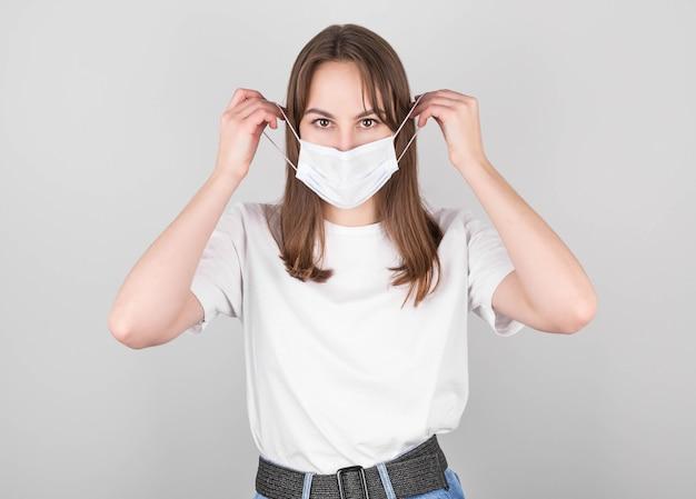Een brunette vrouw in een wit t-shirt en spijkerbroek draagt een antivirusmasker zodat anderen anderen niet besmetten met het coronavirus