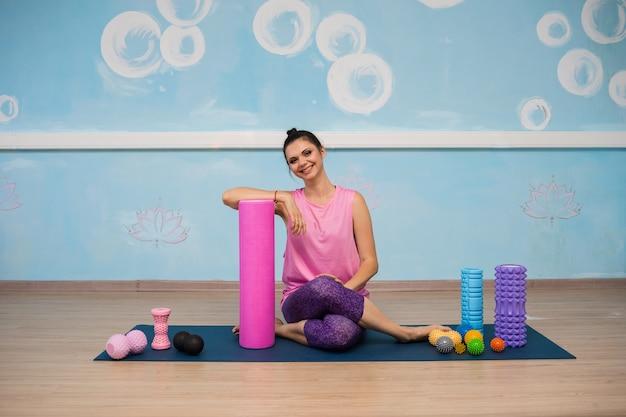 Een brunette vrouw in sportkleding zit op een mat met rugkussens