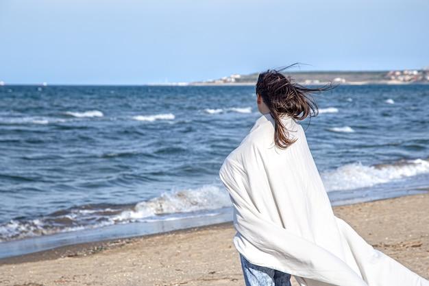 Een brunette vrouw kijkt naar de zee gewikkeld in een deken. achteraanzicht.