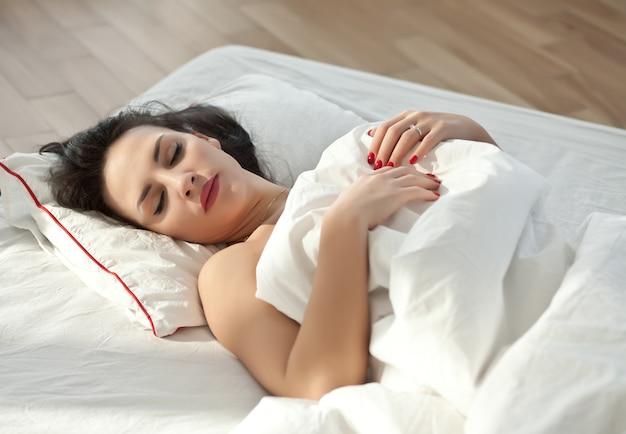 Een brunette vrouw liggend op het bed thuis en slapen.