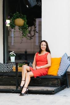 Een brunette vrouw van middelbare leeftijd in een rode jurk zit aan een tafel in een straatcafé, rusten en glimlachen