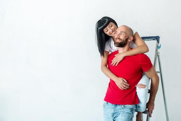 Een brunette vrouw zit op een trapladder en knuffelt de schouders van een bebaarde man tijdens reparaties in de kamer