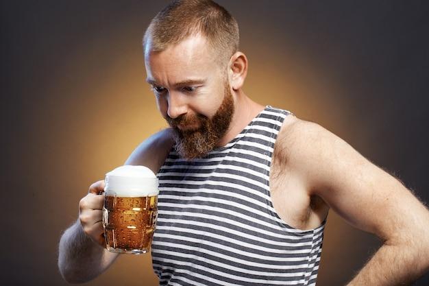 Een brutale man drinkt bier