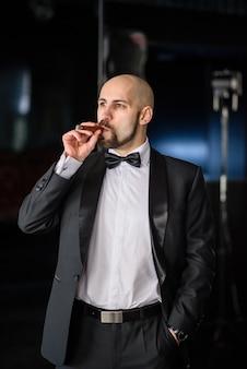 Een brutale man in een geklede jas rookt een sigaar.