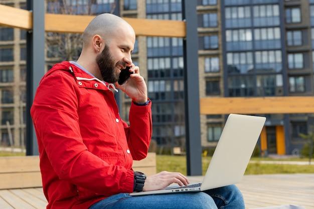 Een brutale man met een baard in alledaagse kleding werkt achter een computer en praat op straat aan de telefoon. concept van buitenshuis werken