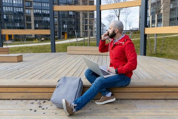 Een brutale man met een baard in alledaagse kleding werkt achter een computer op straat. concept van buitenshuis werken
