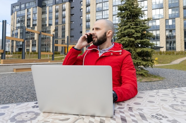Een brutale man met een baard in een rood jasje werkt achter een computer en praat op straat aan de telefoon. concept werkgelegenheid online