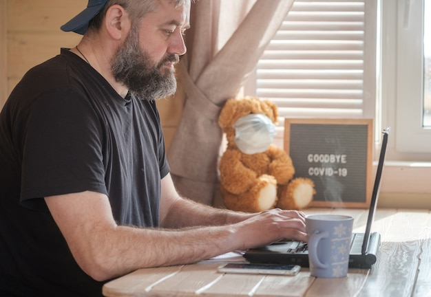 Een brutale man met een baard zit thuis aan een tafel voor een laptopscherm. concept van werken op afstand tijdens quarantaine en pandemie covid-19. online werk vanuit huis