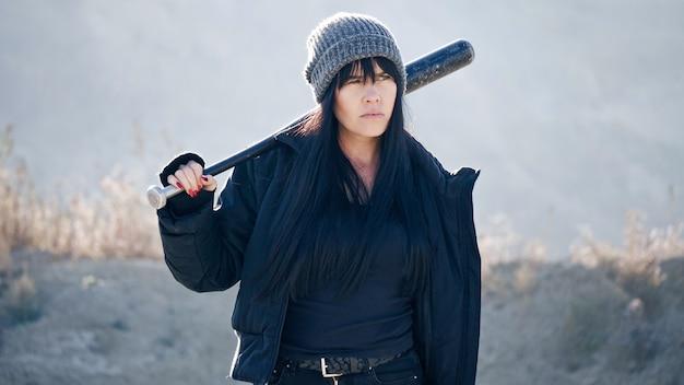 Een brutale vrouw loopt met een honkbalknuppel door de woestenij.