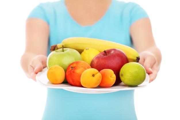 Een buik van een vrouw met een bord fruit op een witte achtergrond