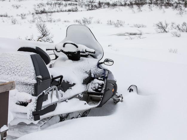 Een buiten geparkeerde sneeuwmobiel is bedekt met sneeuw