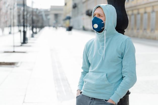 Een buitenopname van hipster draagt een sweatshirt en een ademhalingsmasker, loopt in een epidemische stad, voorkomt virussen, infecties en coronavirus, schrikt van besmetting. qaurantijnse tijd. gezondheid veiligheidsconcept