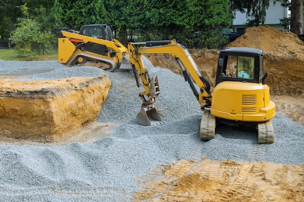 Een bulldozer op wielenvulling van funderingswerkzaamheden op de bouwplaats naar het gebouw in aanbouw.