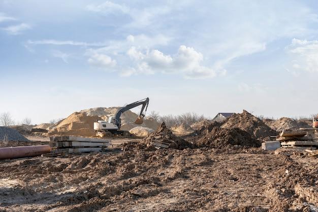 Een bulldozer van een graafmachine die grond graaft en de bouwplaats aan het scheppen is