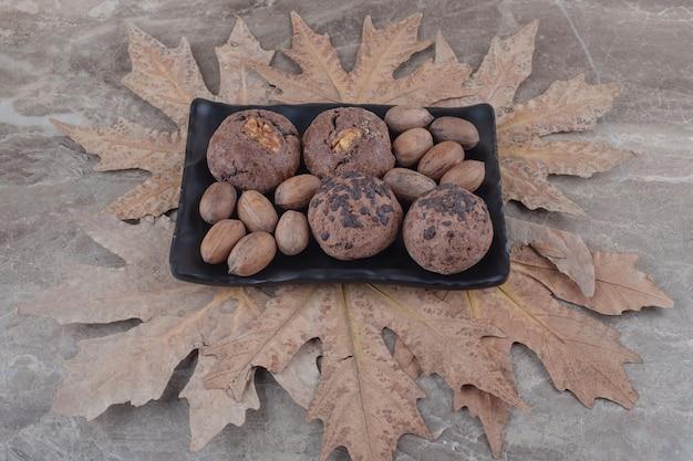 Een bundel koekjes en pecannoten op een schaal en een bos platanenbladeren op marmer