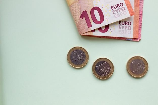 Een bundel van 10 eurobankbiljetten en -munten op een lichte ondergrond