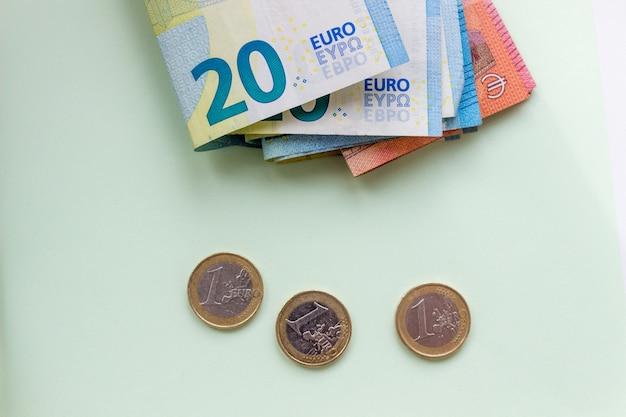 Een bundel van 20 eurobankbiljetten en -munten op een lichte ondergrond