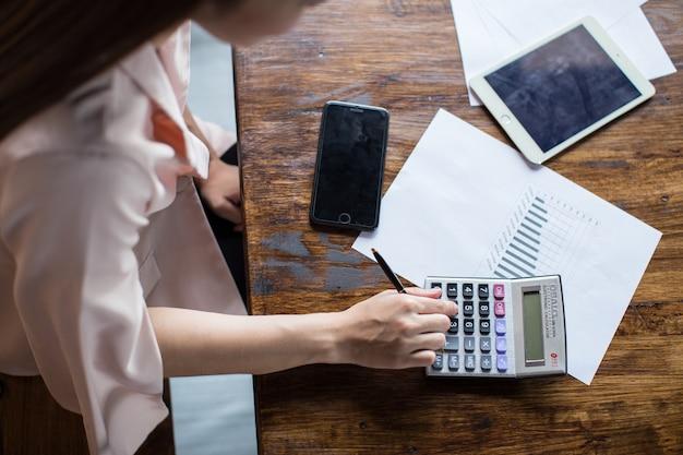Een bureau om zaken te doen met de handen van een jonge vrouw berekent inkomsten en uitgaven.