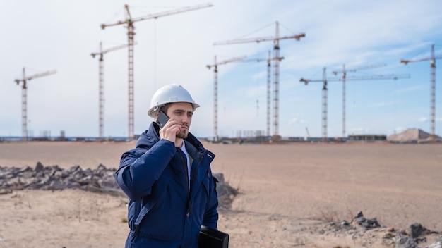 Een burgerlijk ingenieur in een witte helm is in de bouw aan de telefoon.