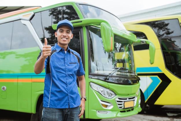 Een buschauffeur in uniform en hoed glimlacht met zijn duimen tegen de bus