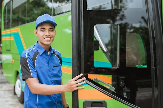 Een buschauffeur in uniform en hoed opende de busdeur toen hij op het punt stond in de bus te stappen