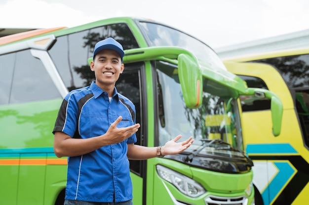 Een buschauffeur in uniform en hoed presenteert met een handgebaar iets tegen de bus