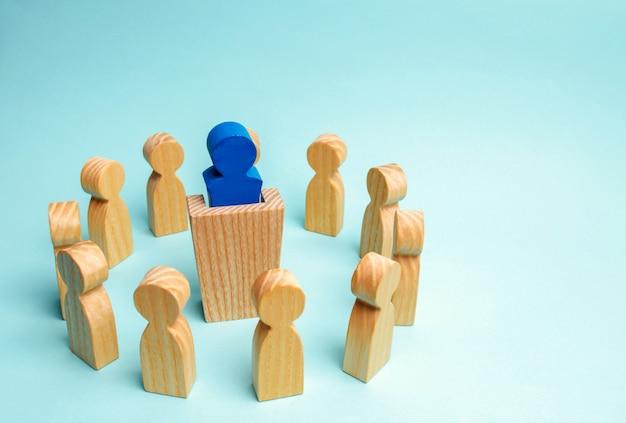 Een businessgroep staat in een cirkel en luistert naar de leider achter de tribune.
