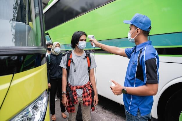Een buspersoneel in blauwe uniformen en een hoed met een thermopistool inspecteert de mannelijke passagier met het masker voordat ze aan boord van de bus gaan