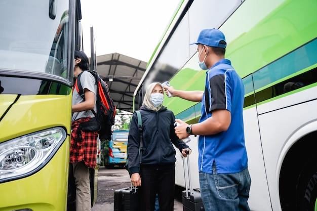Een buspersoneel in uniform en een hoed met een thermopistool inspecteert de passagier van een vrouw met een sluier en masker voordat ze aan boord van de bus gaat