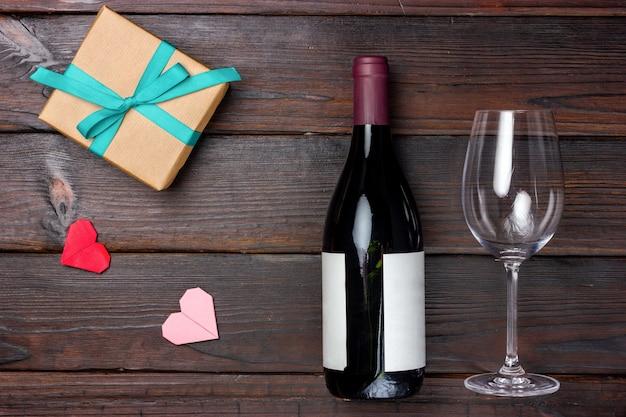 Een cadeau verpakt in knutselpapier, een fles wijn en een wijnglas op een donkere houten tafel. uitzicht van boven.
