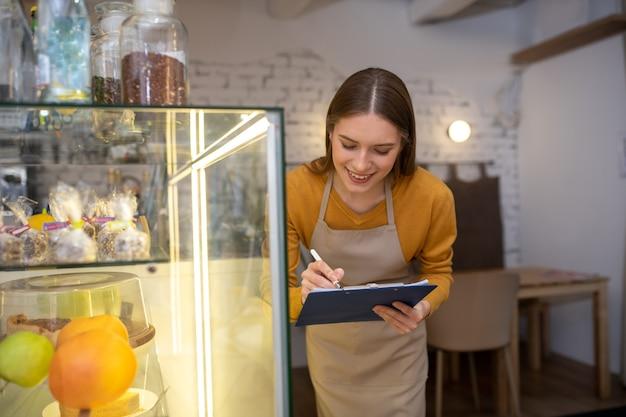 Een café-eigenaar controleert de aanwezigheid van desserts in een vitrine