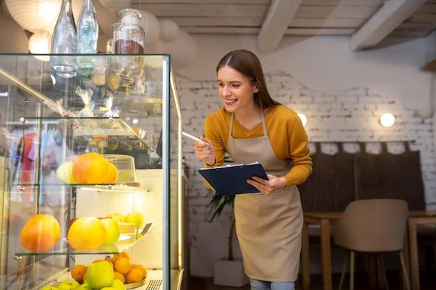 Een café-eigenaar die aan het loket op zoek is naar beschikbare desserts