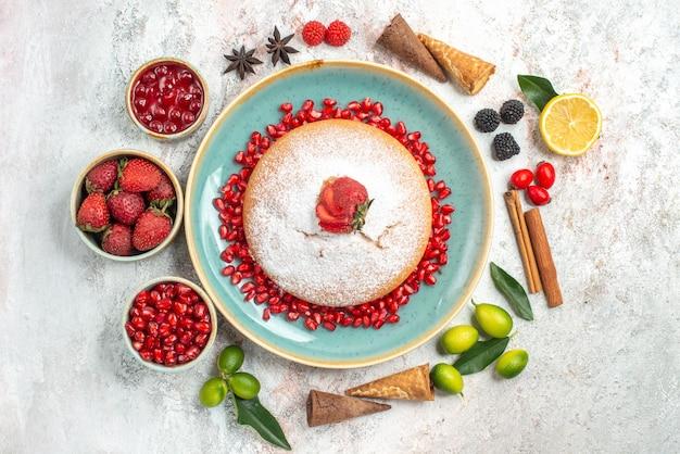 Een cake een cake met granaatappel kaneelstokjes bakjes bessen limoenen steranijs