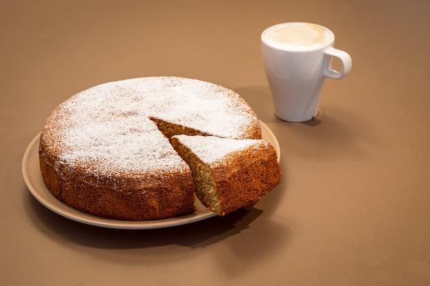 Een cake gemaakt van amandelen en droog brood met een cappuccinokopje op lichtbruine achtergrond