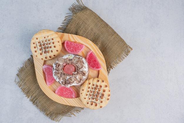 Een cake, koekjes en marmelades op een schotel op marmeren tafel.