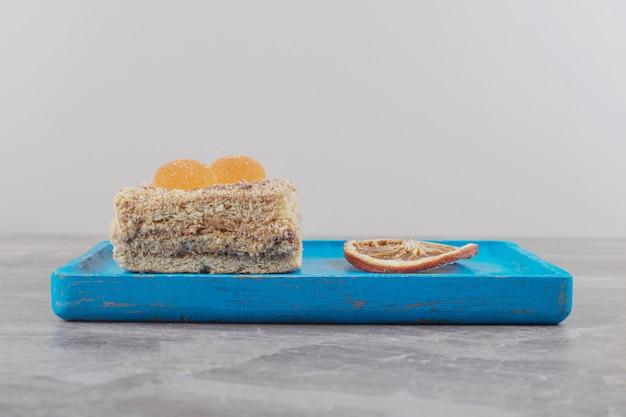 Een cake met marmelades naast een gedroogd schijfje citroen op een blauwe schaal op marmer