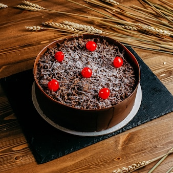 Een cake van de vooraanzichtchocolade die met kersen wordt verfraaid om heerlijk binnen bruine cake pan verjaardags zoete banketbakkerij op de bruine achtergrond