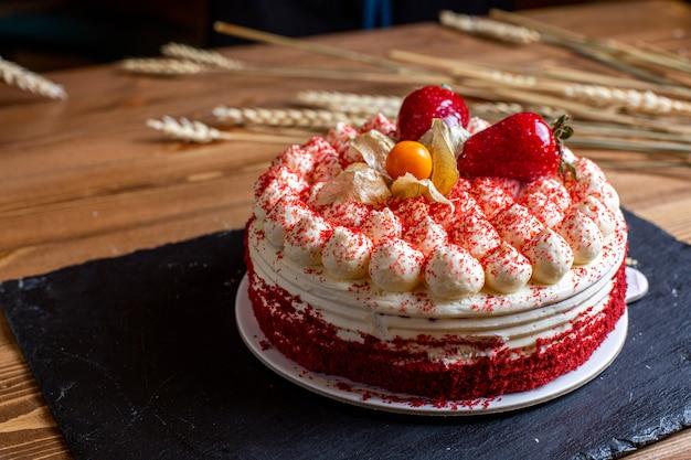 Een cake van de vooraanzichtverjaardag die met roomaardbeien wordt verfraaid om zoete verjaardagsviering