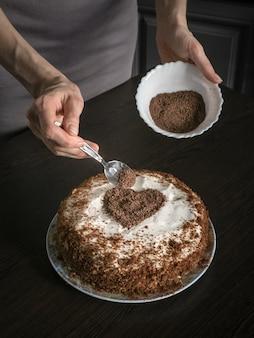 Een cake versieren voor valentijnsdag. met de hand gemaakte pastei met roomkaas het berijpen en een chocoladehart. valentijnsdag concept.