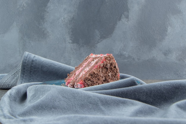 Een cakeplak op een schaal genesteld op een tafelkleed op marmer.