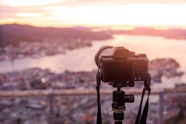Een camera op statief fotografeert een prachtig uitzicht bij schemering