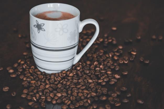 Een cappuccino op een donkere houten tafel met koffiebonen