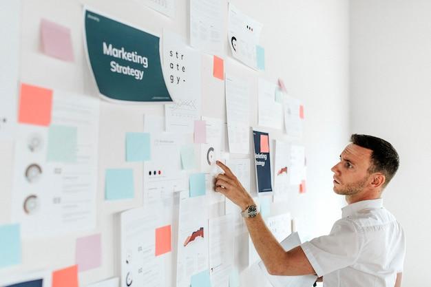 Een casual zakenman die een marketingplan controleert