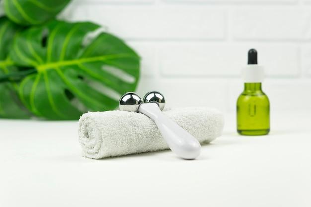 Een cbd groene olie, een roller voor gezichtsmassage, een witte katoenen handdoek en groene bladeren van monstera staan op een witte tafel in een badkamer