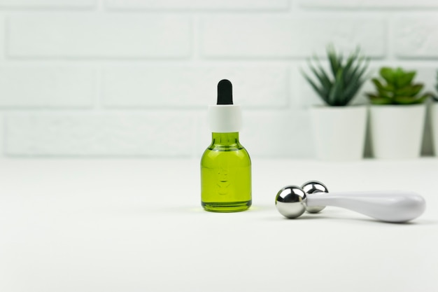 Een cbd groene olie en een face roller staan op een witte tafel