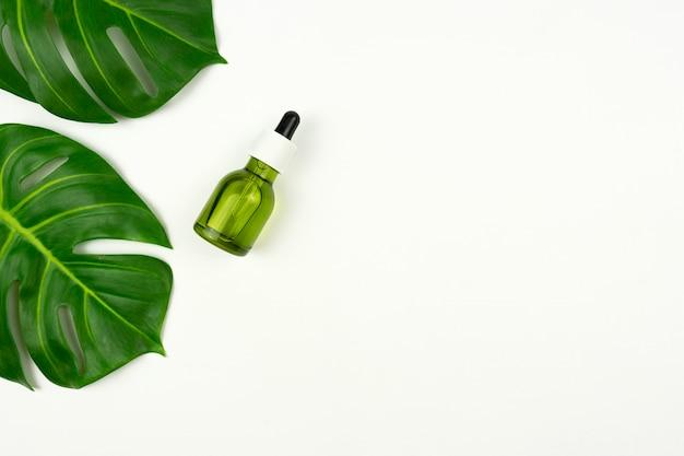 Een cbd groene olie en groene bladeren van monstera liggen op een witte tafel